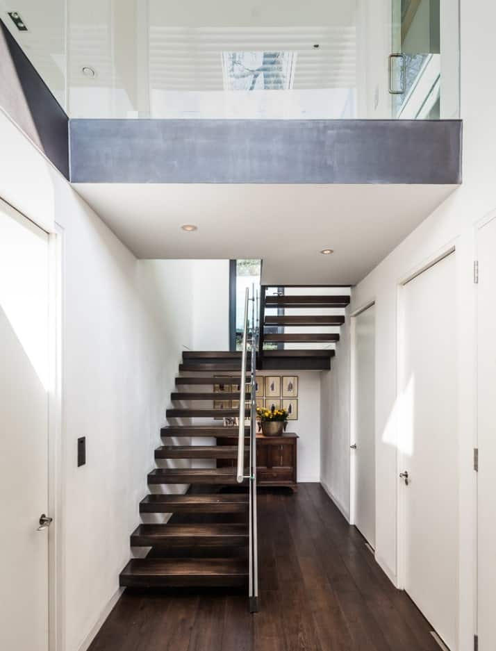 Modern staircase with dark wood treads, open riser and steel handrail along the white walls. There's a wooden cabinet beneath it to save the empty space.