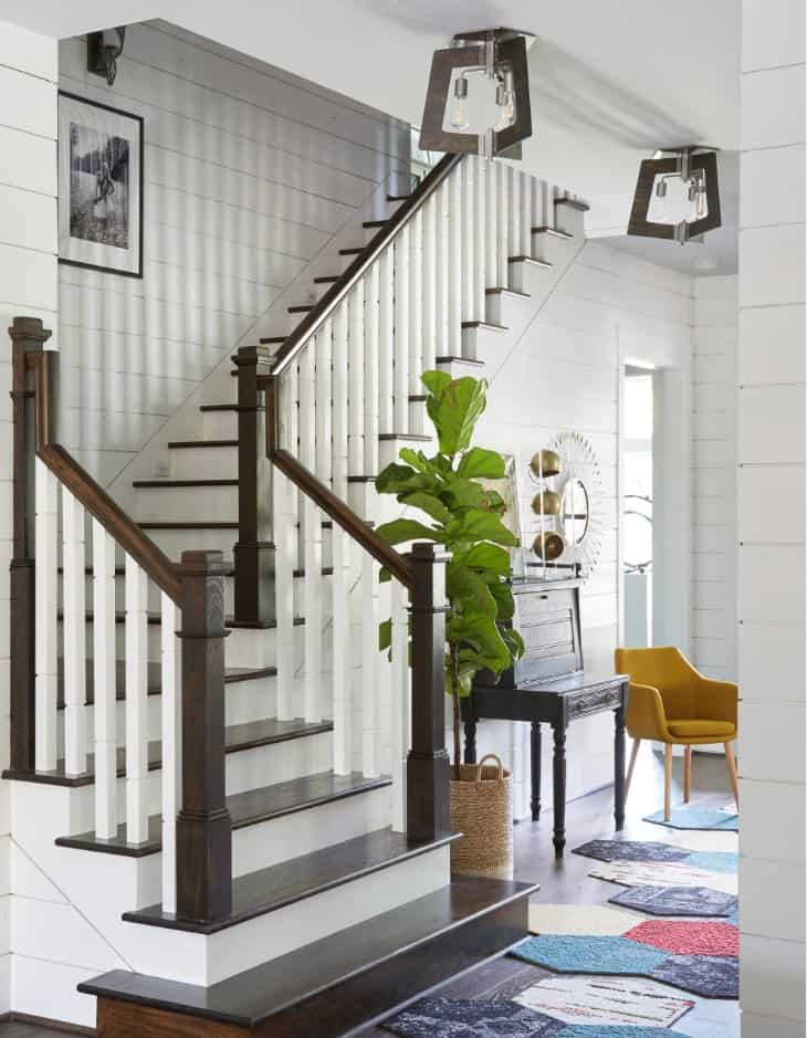 Traditional staircase with white riser and dark wood treads designed with a fiddle leaf fig plant and multi-colored geometric rugs.