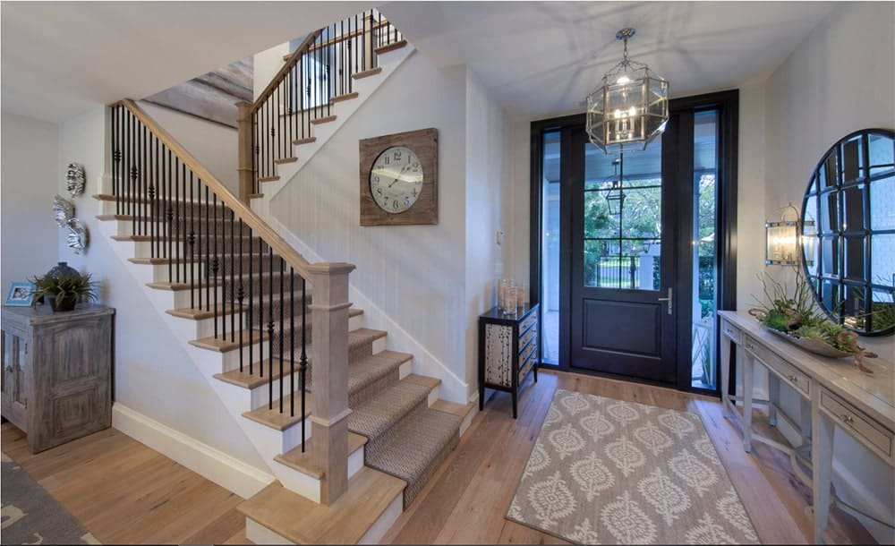 A foyer illuminated by an industrial chandelier features a light wood half-turn staircase with wrought iron spindles and wooden handrailing.