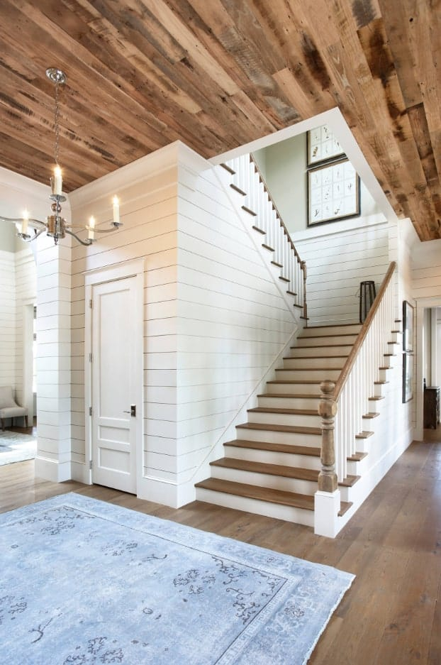 Half-turn staircase accented with shiplap walls and wooden treads along with hardwood flooring. It is lighted by a candle chandelier that hung over a blue rug.