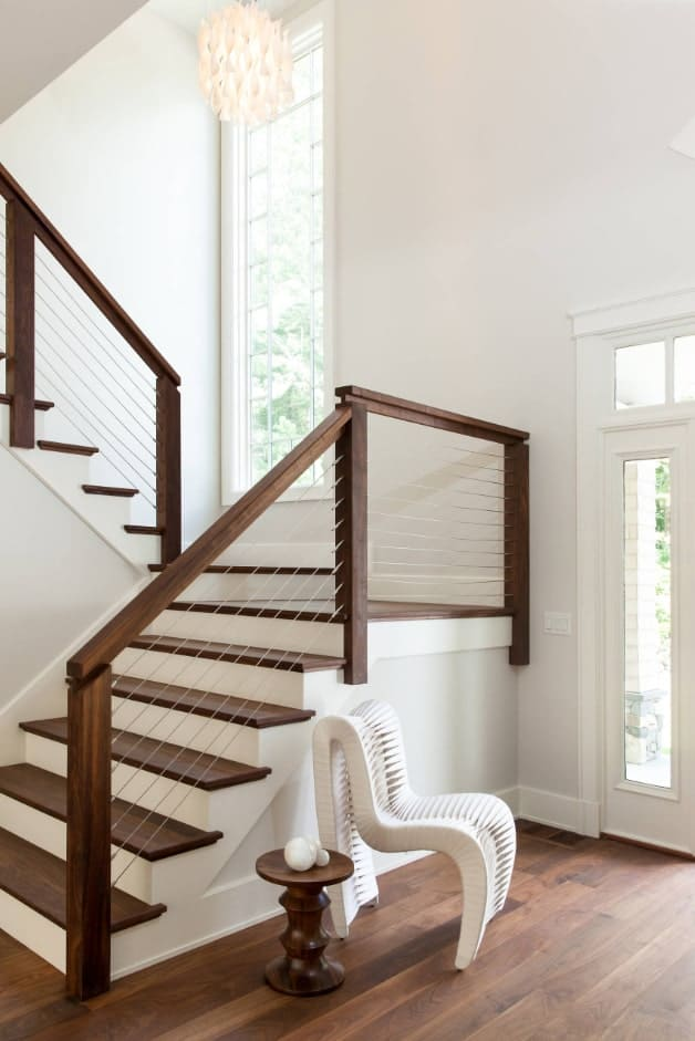 Transitional half-turn staircase with thin steel railings accented with a fabulous peculiar white chair paired with a small side table.