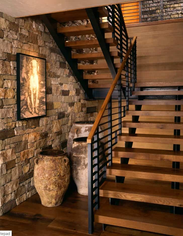 Contemporary staircase with wrought iron railings and wooden treads that matches the walls and floor against an accent brick wall. Vintage jugs beneath it create a rustic feel.