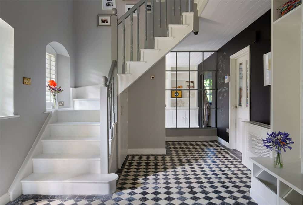 White half-turn staircase accented with a black and white diamond patterned marble tile flooring. It has gray wooden balustrade and built-in storage beneath it.
