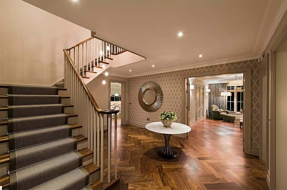 Lovely entrance hall with round center table and patterned walls designed with a sunburst mirror. It features a magnificent half-turn staircase lined with a carpet runner.
