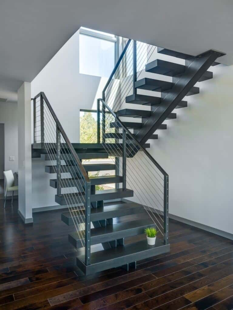 Black wooden half-turn staircase with a modern look. It has single stringer, stainless steel balustrade and an open riser.
