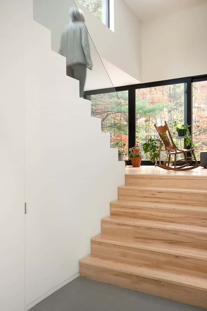 Natural wood half-turn staircase features a frameless glass balustrade against the white walls and glass windows.
