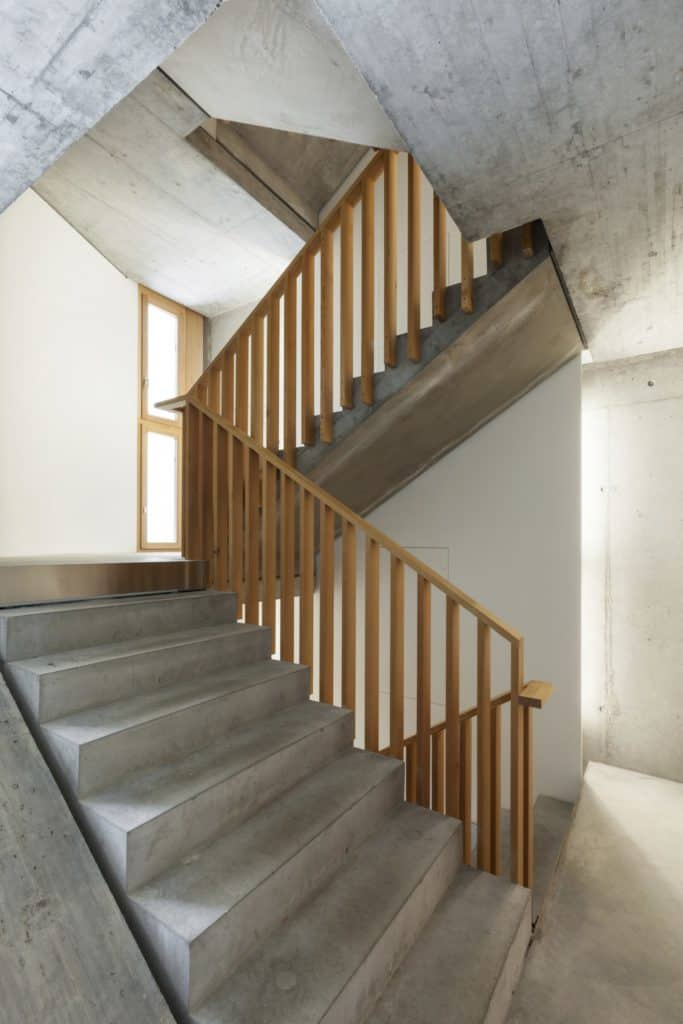 A closeup look of a rustic half-turn staircase with concrete steps and wood balustrade along the white walls.
