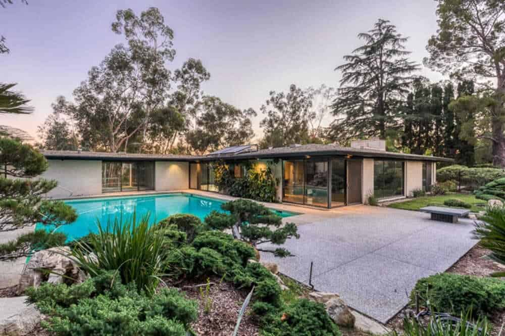 This is a view of the back of the house with an abundance of glass walls and doors facing the backyard that has a large pool complemented by the surrounding shrubs and trees of the landscape.