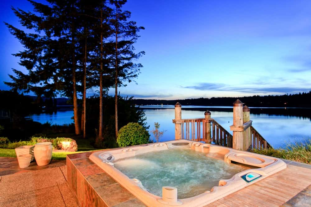 Backyard hot tub with a stunning water view.