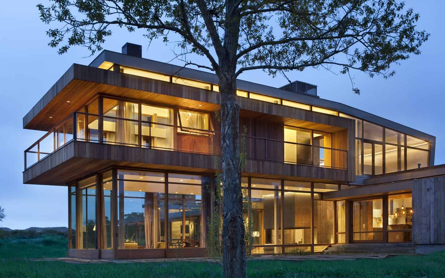 This is the back of the house showing massive floor to ceiling windows accented with wood planks. It sits on an expanive lush lawn.