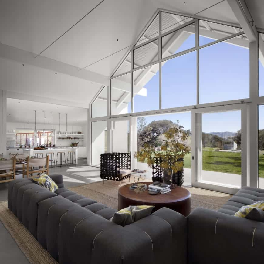 Natural light streams through the full height glass panels illuminating the white interior. It also overlooks the outdoor scenery and allows fresh air to enter through the sliding door.
