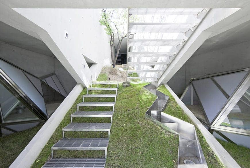 A slope with metal stairs and a zigzag-shaped lighting encasement on its side creating a sleek, modern geometric design.