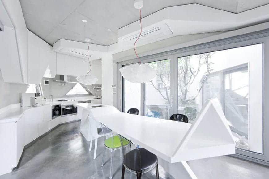 Modern white curved kitchen boasts a lengthy breakfast island that extends as a dining table lighted by floral pendants. Natural light streams through the paneled glass windows.