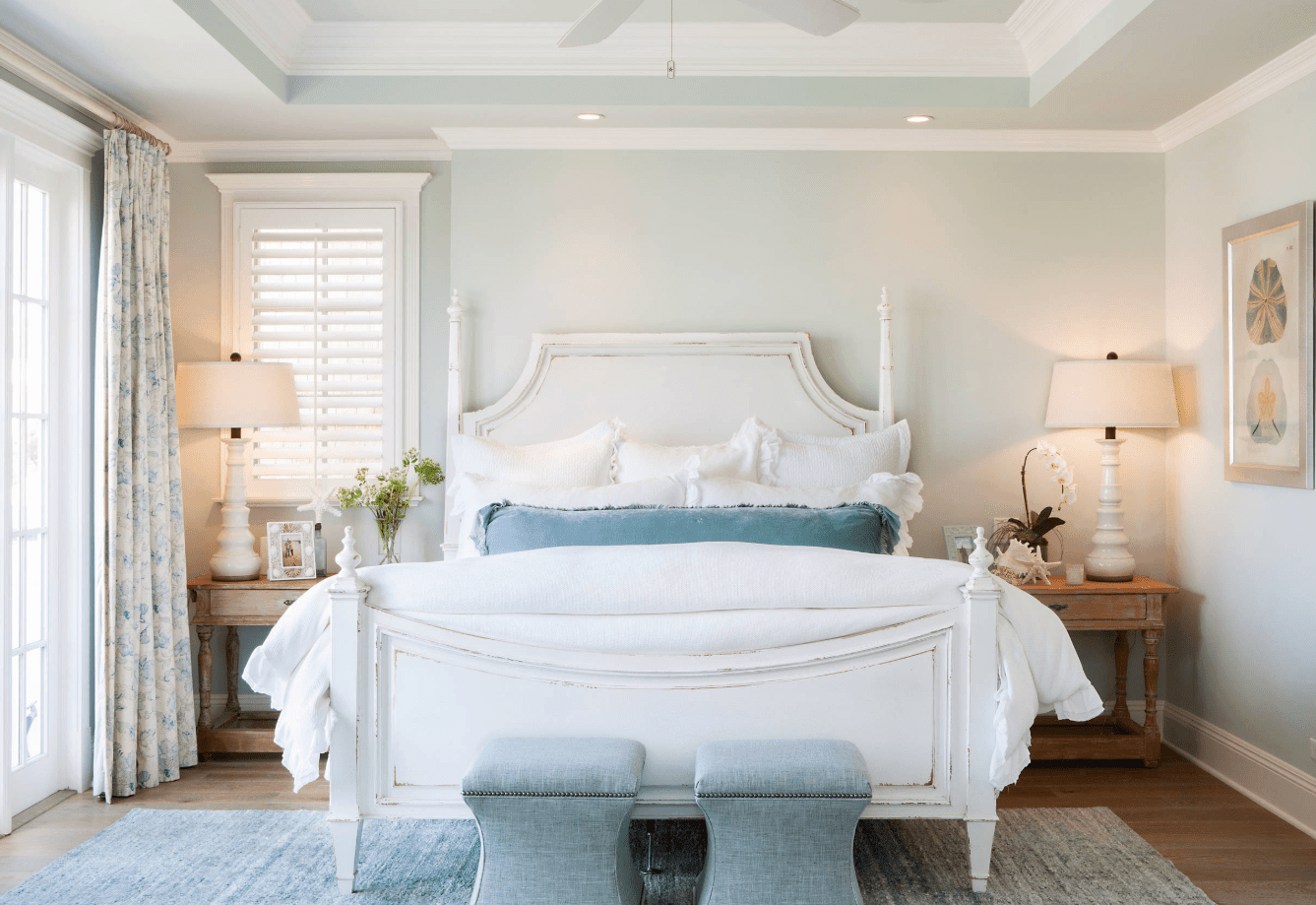 Beach primary bedroom features white bed surrounded with light blue walls and framed windows. It sits on a gray rug over hardwood flooring.