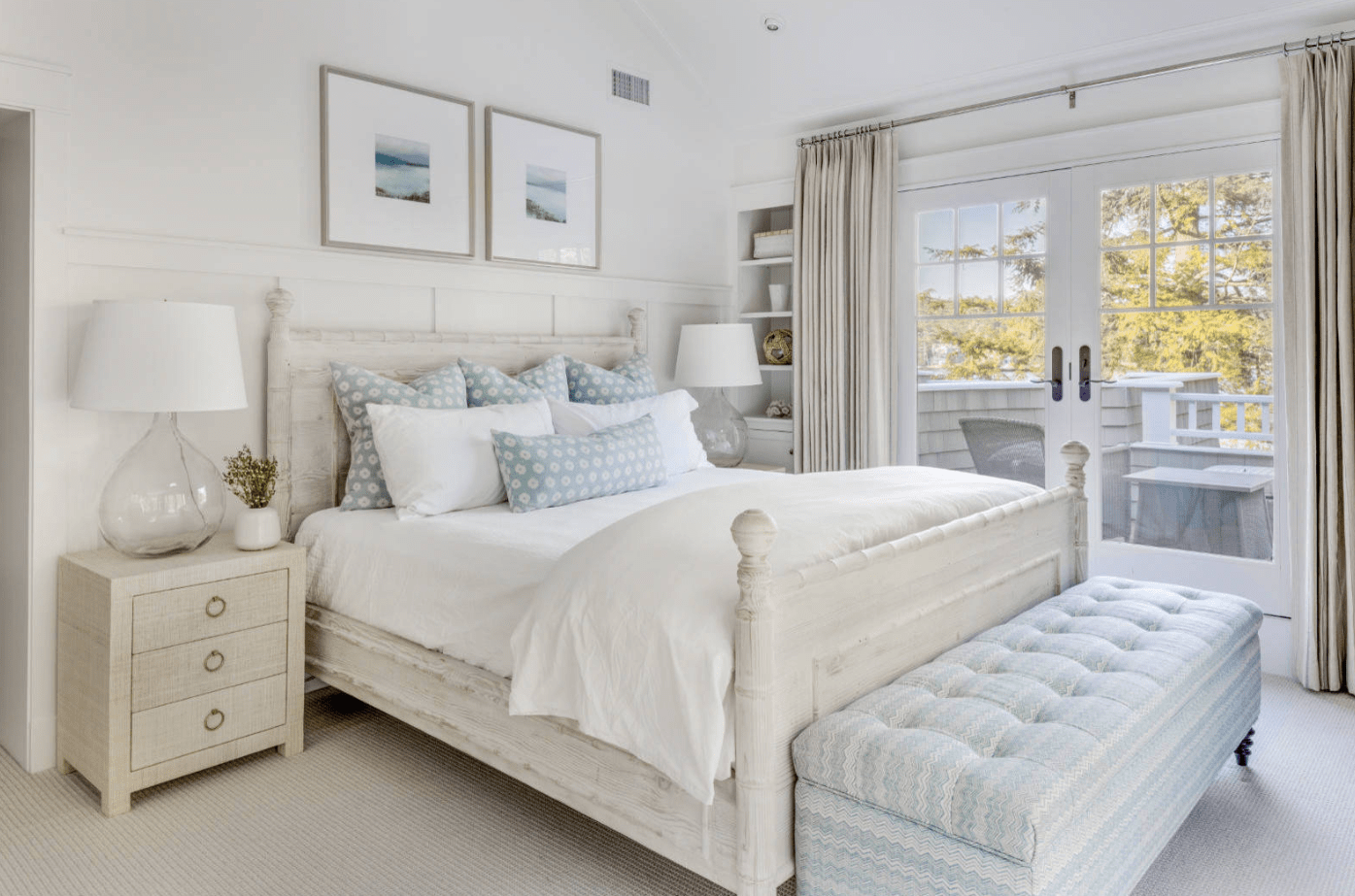 Charming primary bedroom with wooden bed and a lovely blue tufted bench on its end. It includes wooden nightstands with round glass table lamps and carpet flooring.
