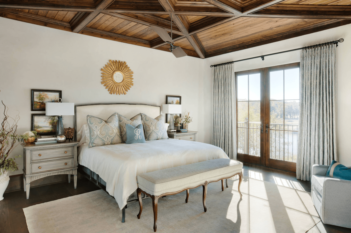 Cozy primary bedroom designed with a gold sunburst wall mirror and wooden coffered ceiling. It has glass doors that bring natural light in.