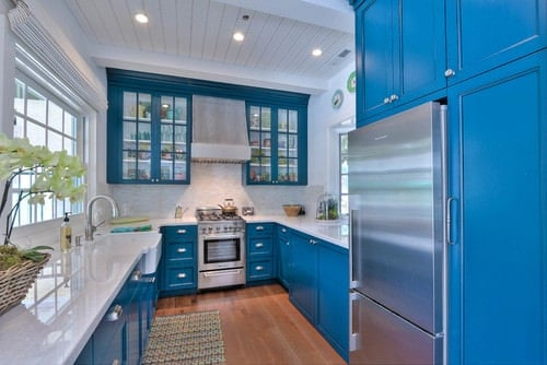 Gorgeous kitchen boasts vibrant blue cabinetry and pearl white countertop along with hardwood flooring and shiplap ceiling.