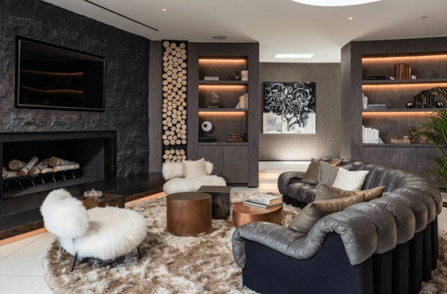 Elegant living room showcases a black textured wall fitted with a television and fireplace. It is furnished with a curved sofa, various shaped coffee tables and a pair of white faux fur chairs over a round brown shaggy rug.