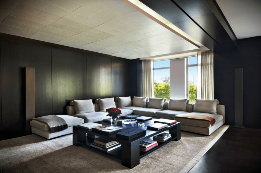 A contemporary living room filled with a beige L-shaped sectional and a quadri coffee table. It has a floor to ceiling windows covered in sheer curtains.