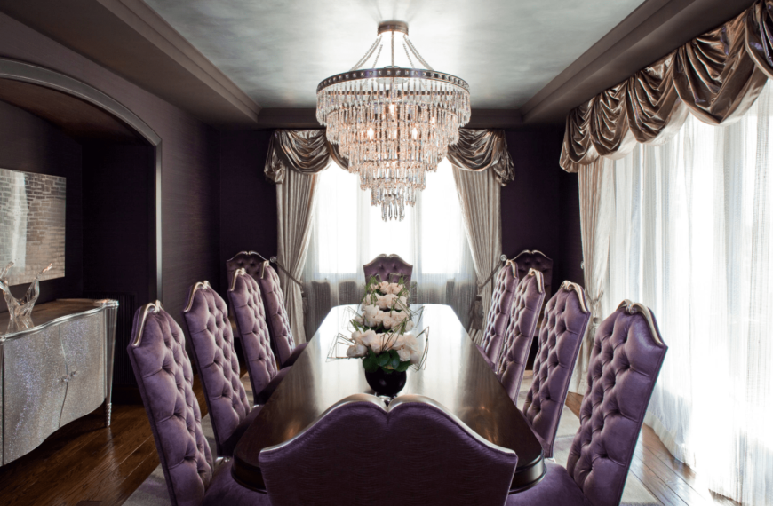 Elegant and sophisticated, this dining area has a long wooden table for ten, a luxurious set of purple upholstered chairs, and a fancy chandelier.