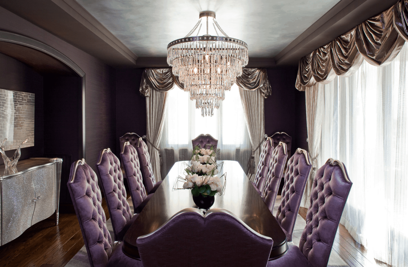 A glamorous purple dining room featuring a luxurious dining table and chairs set lighted by a grand chandelier.
