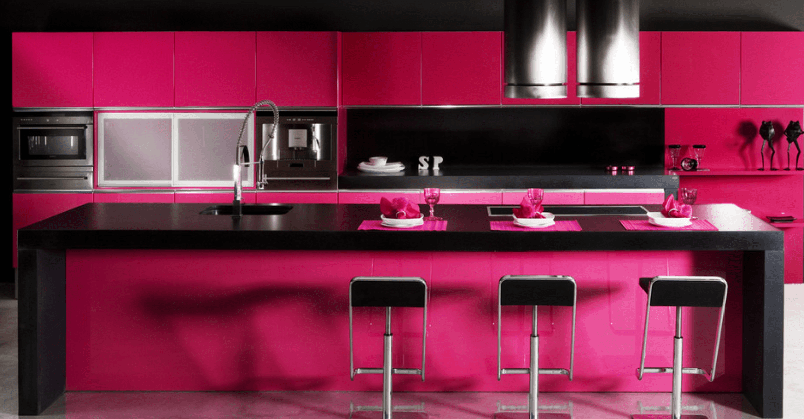 Hot pink kitchen with a black countertop breakfast island aligned with black metal bar stools. It is fitted with a sink and cooktop below round stainless steel vent hoods.