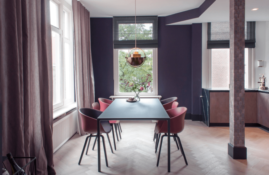 A dining room with different hues of pink and purple, with a rectangular table, unique chairs, and a statement pendant light.