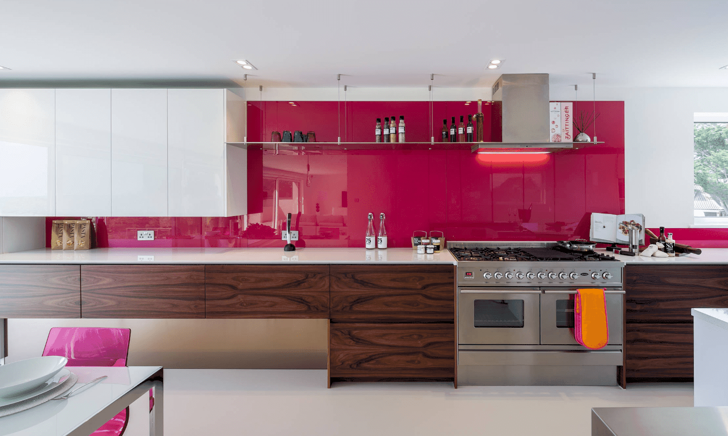 Elegant kitchen highlighted by a glossy magenta backsplash. It has white upper cabinetry and wood stained lower cabinetry topped with white marble counter.