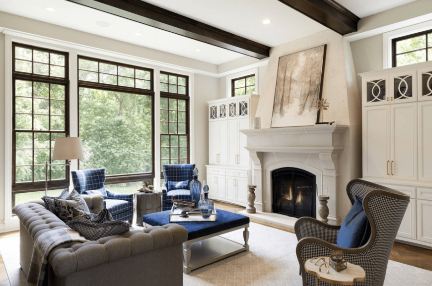White craftsman living room accented by a gray tufted sofa and checkered blue armchairs that accents the velvet blue center table. It has a modern fireplace placed between elegant white cabinets.