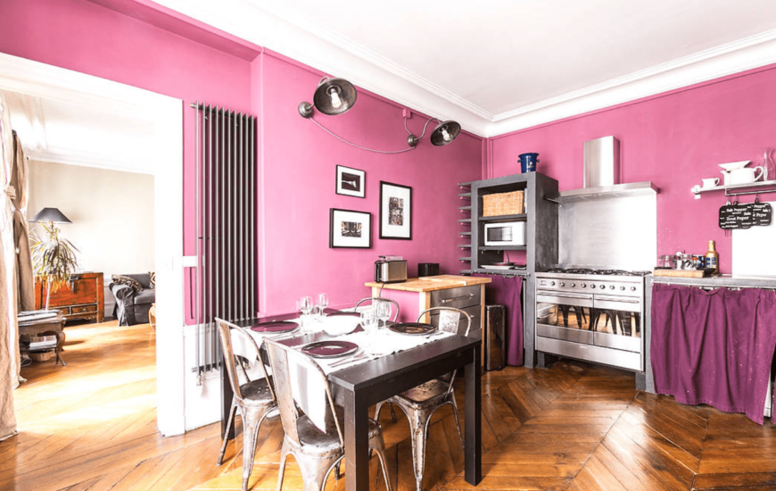 The eat-in kitchen features pink walls designed with black and white frames along with herringbone wood flooring.