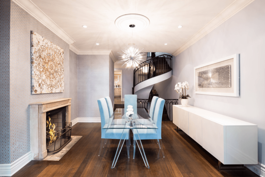 A chic modern dining room with a fireplace, glass table, sky blue upholstered chairs, printed light purple walls, and a bright pendant light.
