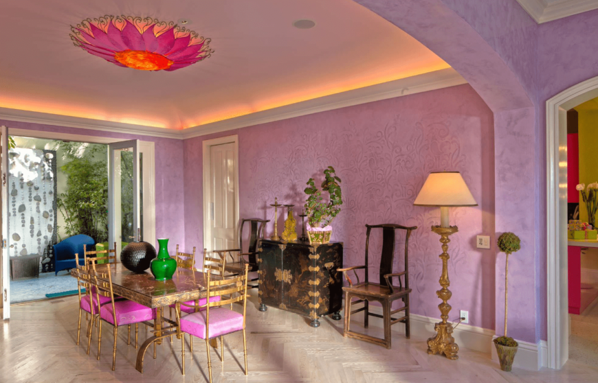 A purple dining room with surprising pops of colors such as bright greens and pinks. It has upholstered golden metallic chairs, hardwood flooring, and an interesting flushmount light.