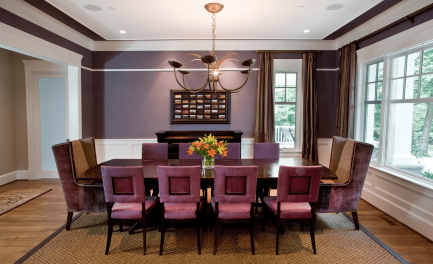 A cozy dining area with purple walls and purple velvet chairs, wooden rectangular table for ten, and hardwood floors.