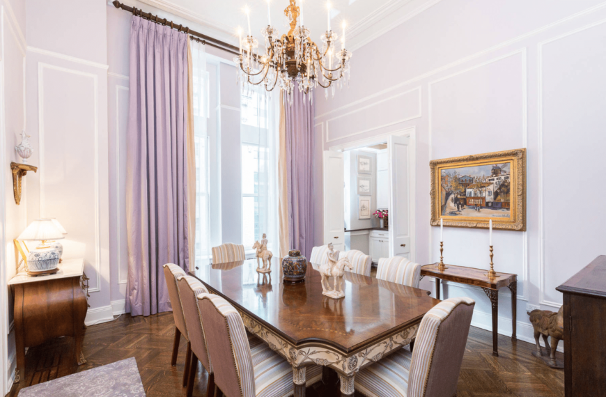 Victorian inspired dining room with a classic chandelier, wooden table, upholstered chairs in stripes, hardwood flooring, and a huge window covered by a light purple curtain.