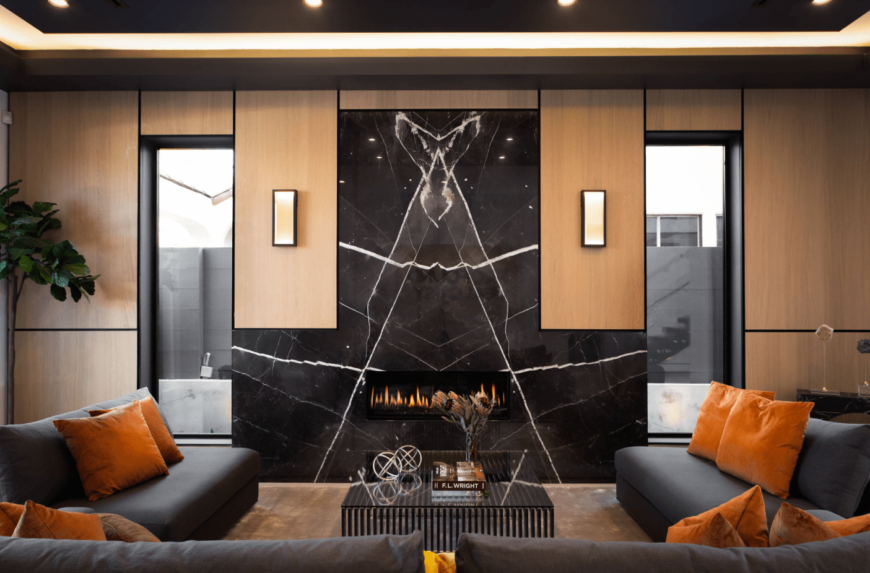 Warm living room boasts a black marble accent wall fitted with a modern fireplace. It has elegant wood wall panels illuminated by sconces and recessed ceiling lights.