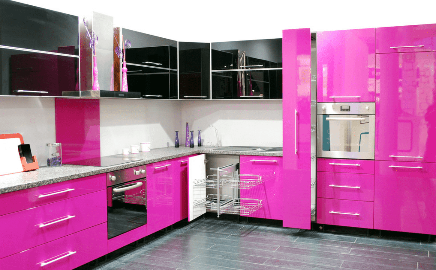 Striking kitchen offers a marble countertop along with black and fuschia pink cabinetry. It has a stainless steel vent hood topped with lovely vases.