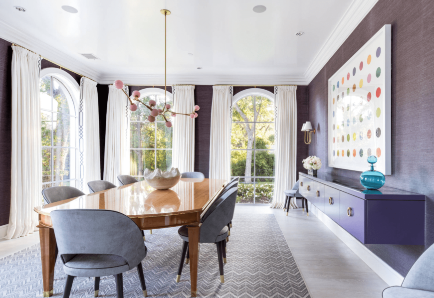 A chic wide dining area with different tones of purple, from its chairs, walls, cabinets, and a statement chandelier. The tall arched windows make the room bright and inviting.