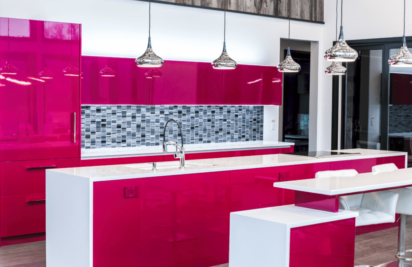 Contemporary kitchen boasts high gloss metallic pink cabinetry accented with a black checkered backsplash. It has a kitchen island bar illuminated by silver pendants.