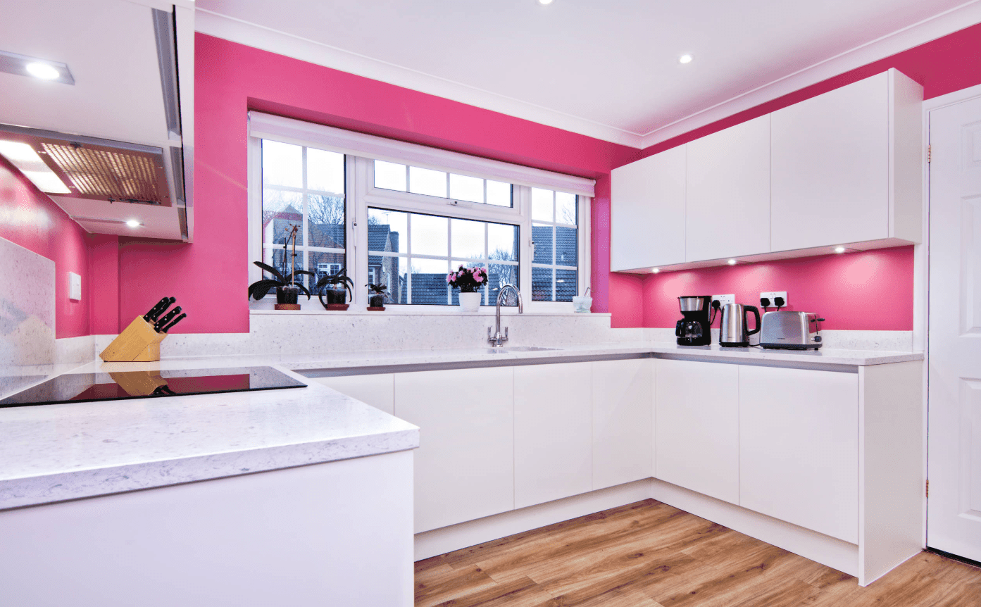 Modern kitchen with pink walls and hardwood flooring. It includes white cabinetry with built-in lights and marble countertop.