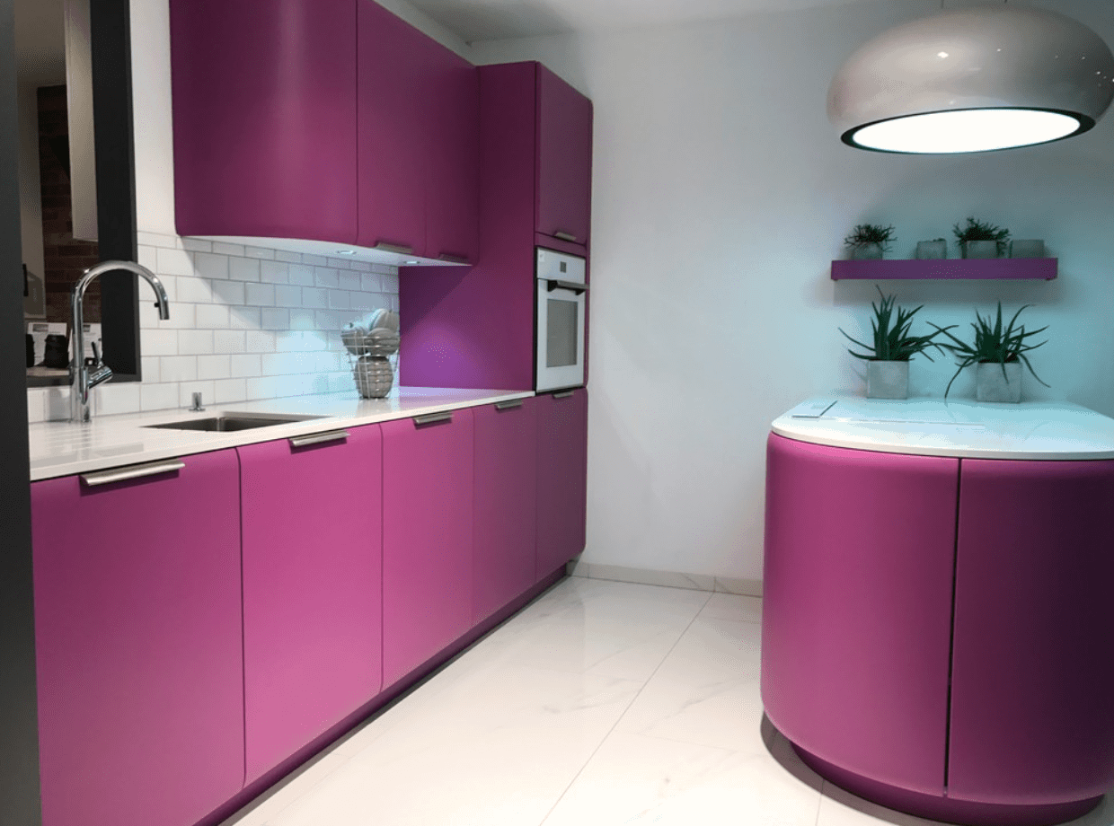 Sleek kitchen showcases an oversized dome pendant that hung over the peninsula. It includes white subway tiles fitted between rose pink cabinetry.