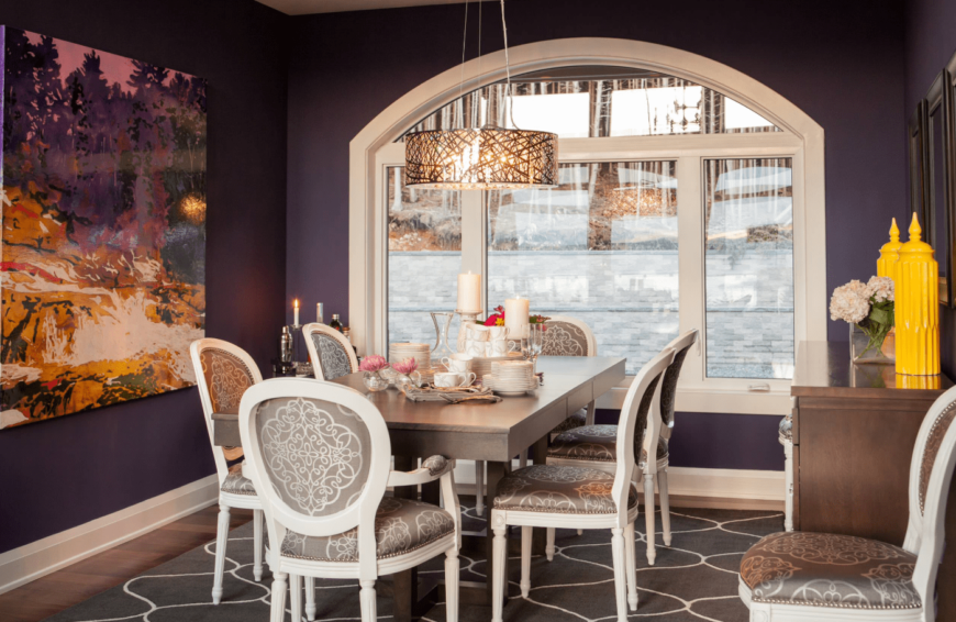 A purple dining room with pops of yellow accents, stylish gray upholstered chairs paired with a gray wooden table, and a unique pendant light.