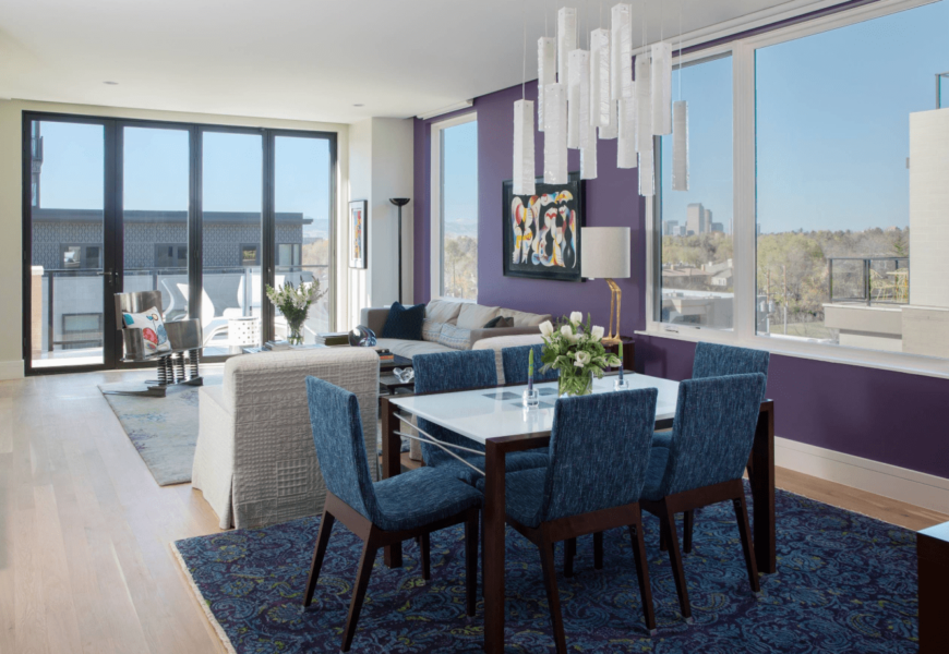 A mini dining area with bluish-violet upholstered chairs, a rectangular table for six, and a statement chandelier.