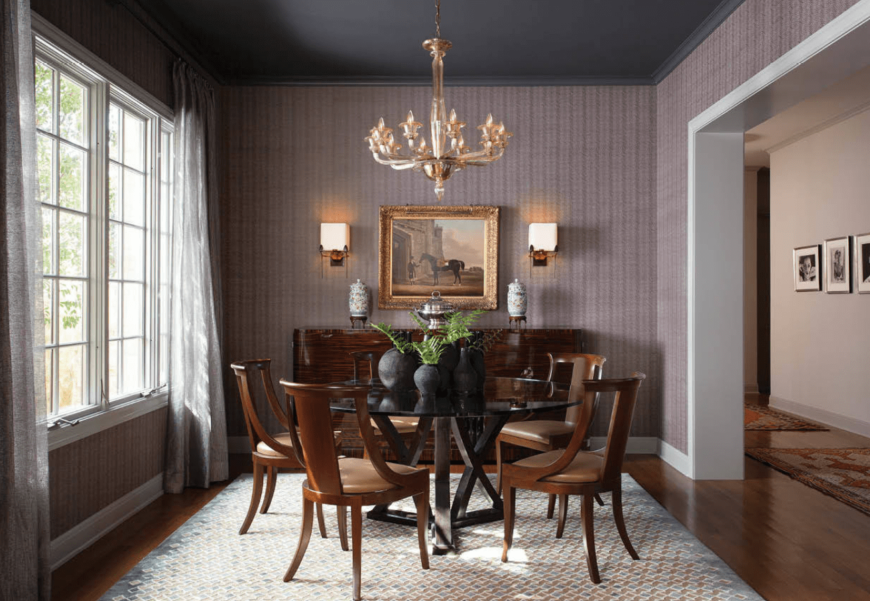 Dining area with light purple walls, a round glass table, antique wooden chairs, hardwood floors, and a chandelier.