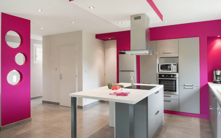 Glam kitchen boasts hot pink walls styled with round holes. It has a gray breakfast island that complements with the cabinetry.