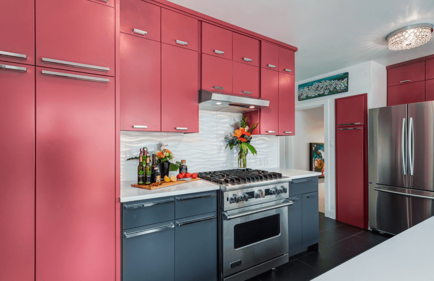This kitchen is filled with salmon pink and gray cabinetry with white wavy backsplash tiles and stainless steel appliances.