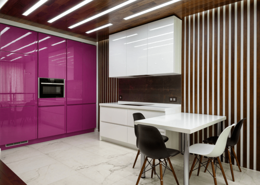 Gorgeous kitchen features pink and white cabinetry fixed to the vertical wood paneled wall. It is illuminated by linear recessed lights attached to the wooden ceiling.