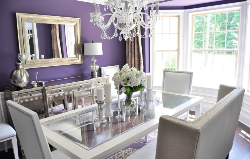 A touch of Victorian style, this dining room has purple walls, paired with a purple rug, a classic chandelier, and a chic glass table.