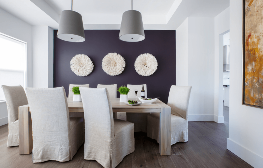 A clean design dining room with one wall painted with dark purple, a fancy white wall art, two simple pendant lighting, hardwood floors, and a wooden rectangular table.