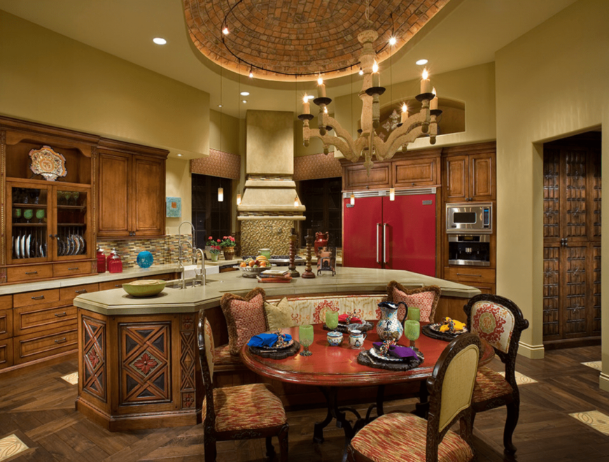 Southwestern kitchen features wood cabinetry along with a carved wood breakfast island. It is complemented by a lovely candle chandelier and a dining space.