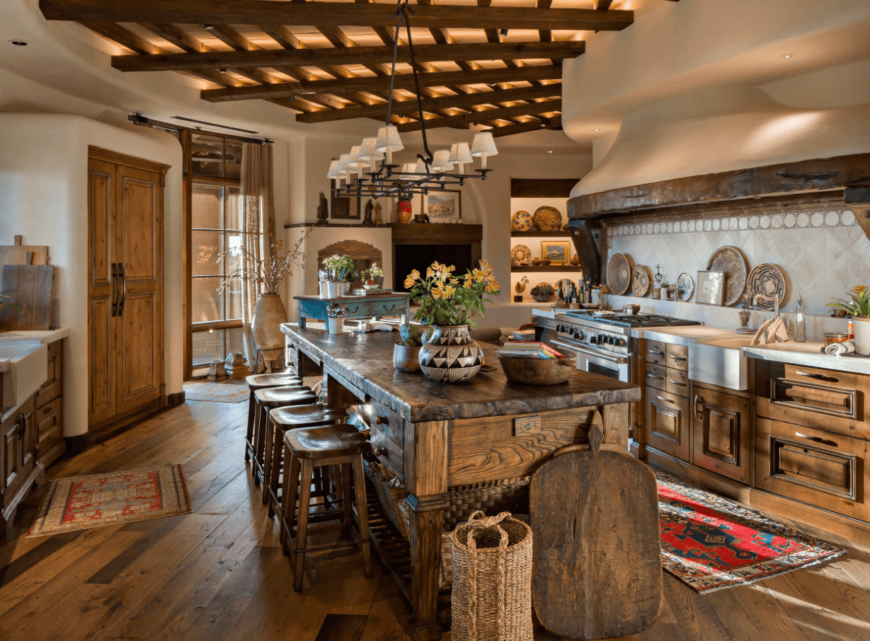 Fabulous kitchen accented with a wooden suspended ceiling. There's a rustic chandelier that hung over a breakfast island aligned with wooden counter stools.
